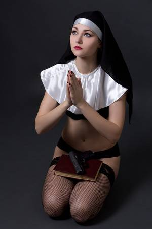 37508626-beautiful-sexy-woman-nun-in-lingerie-praying-with-bible-and-gun-over-grey-background